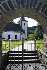 Blick durch das Friedhostor auf die Pfarrkirche St. Vincentius in Lenne