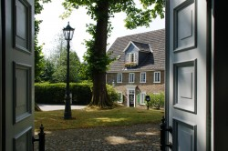 Blick durch die Kirchentür auf das ehemalige Pfarrhaus