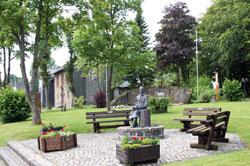 Dorfgarten mit Löffelschnitzerskulptur und dem Ehrenmal neben der Martin-Luther-Kirche in Langewiese